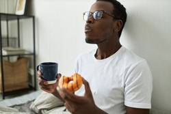 Indoor shot of stylish hungry young dark skinned man in glasses eating glazed orange doughnut with great relish, closing eyes with pleasure, enjoying every bite of sweet dessert, drinking morning tea