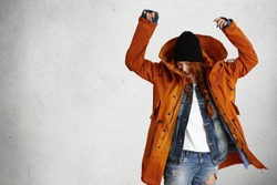 Indoor shot of stylish young woman model wearing fashionable red winter coat, black hat and ragged jeans having fun, lifting her hands up while posing isolated against grey studio wall background