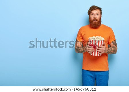 Indoor shot of surprised ginger man watches horror film alone, feels scared, eats popcorn from bucket, spends day off at home, stands over blue background with blank space. Emotions in cinema #1456760312