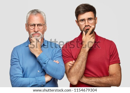 Indoor shot of two partners of different age, hold chin and look with displeased expressions, cant find solution of problem, stand next to each other, isolated over white background. Emotions concept