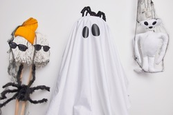 Indoor shot of very scary ghost with spooky black spider on head ready for Halloween carnival or costume party poses against handmade creepy creatures. Celebration holiday and mystery concept