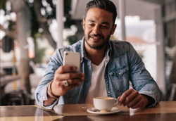 Indoor shot of young man sitting in coffee shop reading text message on mobile phone. Handsome caucasian guy at cafe using smart phone.