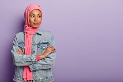 Indoor shot thoughtful beautiful Arabian female stands indoor with crossed hands, focused away, contemplates about future plans, wears hijab and denim coat, isolated over purple studio wall.