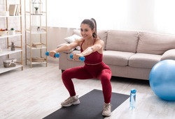 Indoor sports concept. Strong young woman working out with dumbbells at home, doing squats exercise