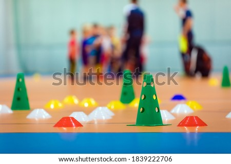 Indoor sports training pitch. Sports training equipment. Practice futsal field. Colourful training markers and cones. Kids sports team on training in blurred background. School sports education
