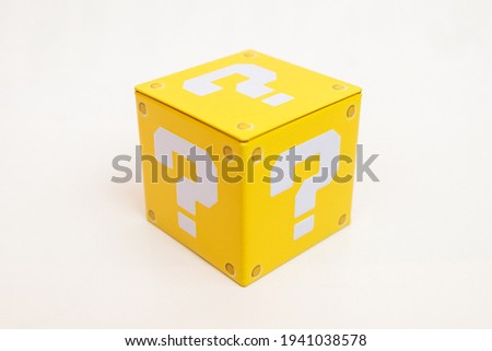 Indoor still-life photo of a yellow box with a big white question mark printed on each face. It recalls a graphic element of a famous platform video game.