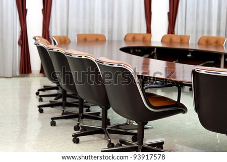 Indoors - Conference hall with oval table and leather chairs.