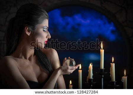 Indoors portrait of a sorceress with the glass sphere and the candles