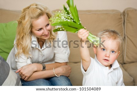 Indoors portrait of young child with his fashionable young mother.