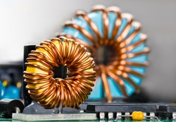 Inductors detail. Copper wire winding. Magnetic ferrite core. Inverter. Beautiful colored coils in dismantled electric power supply unit. Colorful electronic parts. Chips, capacitor. Selective focus.