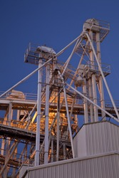 industrial abstract - top of a grain elevator with gravity flow pipes at night