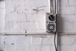 Industrial 10 amper power outlet mounted to a workshop wall with copy space