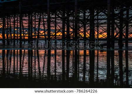 Industrial architectural geometric lines and angles of pylons under pier structure on reflected on wet sand beach at sunset #786264226