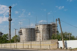 Industrial area in the city. Elevator tanks for grain storage. Big pipe. Fenced territory of the industrial zone. Blue sky and clouds over the industrial area
