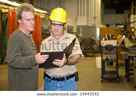 Industrial auditor discussing his inspection results with the factory owner.