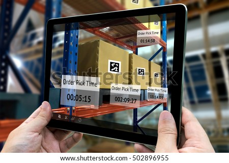 Industrial 4.0 , Augmented reality and smart logistic concept. Hand holding tablet with AR application for check order pick time in smart factory background