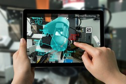 Industrial 4.0 , Augmented reality concept. Hand holding tablet with AR service , Thermal Monitoring motor application for check destroy part of smart machine in smart factory background