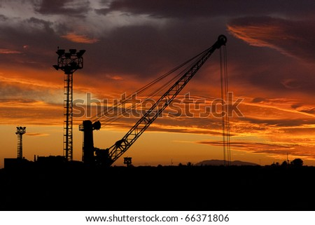industrial background: Construction site with building crane and steel frames rising up against a sunset with cloudy orange sky