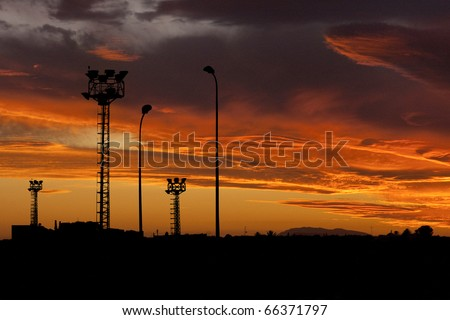 industrial background: Construction site with steel frames rising up against a sunset with cloudy orange sky