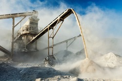 Industrial background - crusher (rock stone crushing machine) at open pit mining and processing plant for crushed stone, sand and gravel