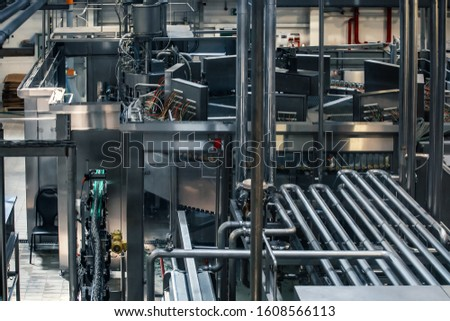 Industrial background of beer factory or plant production with computerized automation process, stainless steel vats, reservoirs, pipelines, tubes and modern robotized technologies and electronics