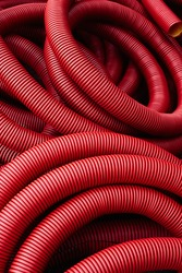 Industrial background - red plastic corrugated pipes