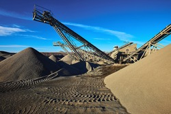 Industrial background with working gravel crusher. Extraction of gravel. Conveyor for transporting gravel. Morning. Beautiful light.