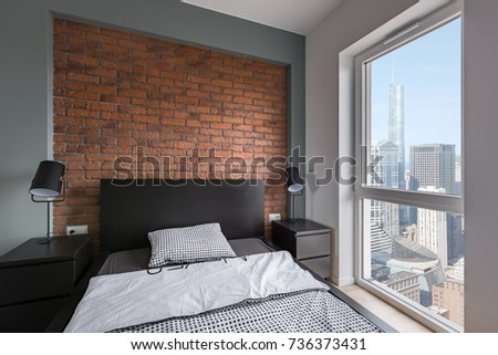 Industrial bedroom with bed, red brick wall and window #736373431