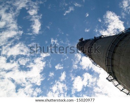 Industrial big chimney in background blue sky white clouds