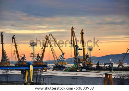 Industrial black sea port Burgas, Bulgaria with a lot of cranes, cabins, boxes and tanks on beautiful orange sunset