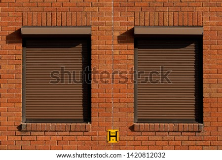 Industrial building exterior windows with brown security shutter.