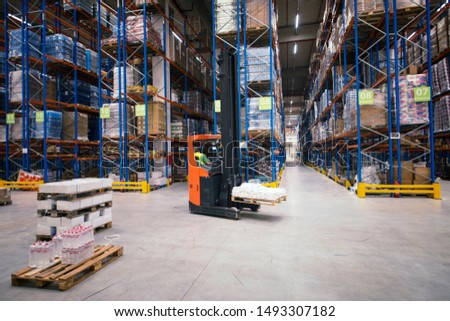 Industrial building large warehouse interior with forklift and palette with goods and shelves. Storage goods and distribution.
