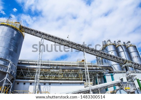 Industrial building on a background of blue sky. Bottom view of the metal structural elements, tanks, pipes, parts and stairs of a modern plant.