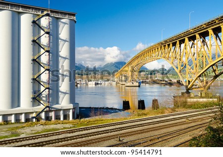 Industrial Building over empty railways and nice yellow bridge across the inlet in Vancouver, Canada.