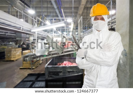 Industrial butcher posing with two filleting knives, wearing protective and hygienic clothing, such as a white suit, mask and a yellow hard hat, in front of a large animal processing plant