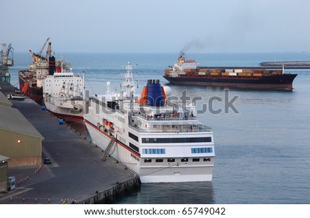 Industrial cargo ships and big white cruise liner at a port in Abu Dhabi
