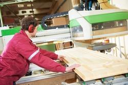 industrial carpenter worker operating wood cutting machine during wooden door furniture manufacturing