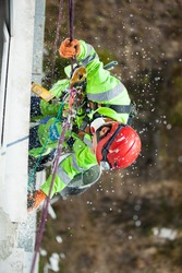 Industrial climber during winterization works, cutting styrofoam boards and styrofoam dust falling down