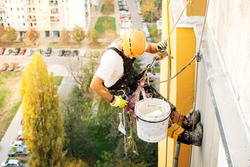 Industrial climber hanging on the rope while painting the exterior facade wall of the tall apartment building. Industrial alpinism and high risk work scene concept image