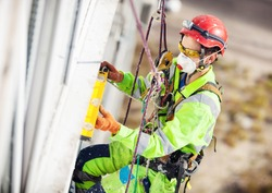 Industrial climber measuring with level tube during construction works