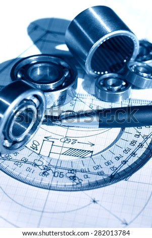 Industrial concept. Few ball bearings near ruler on graph paper background