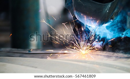 Industrial concept: worker in helmet repair detail in car auto service, close uptelephoto #567461809