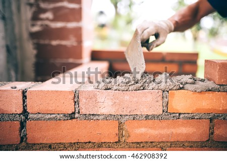 industrial Construction bricklayer worker building walls with bricks, mortar and putty knife ストックフォト ©