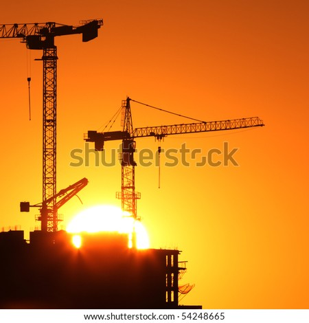 Industrial construction cranes and building silhouettes over sun at sunrise.