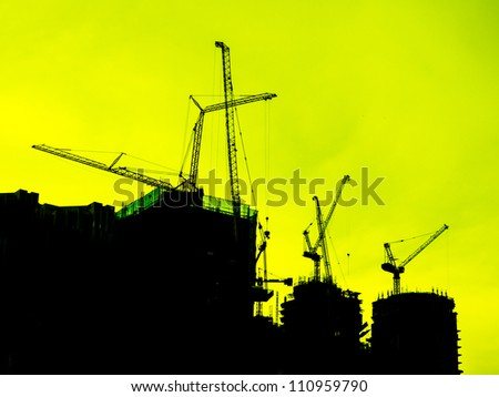 Industrial construction cranes and building silhouettes over yellow sky