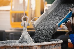 Industrial construction machinery workers pouring cement concrete using a concrete bucket