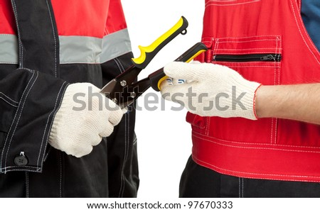 Industrial/construction workers in uniform holding special tool; closeup of men\'s hands holding/giving/taking wire cutter isolated on white