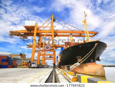 Industrial Container Cargo freight ship with working crane bridge in shipyard with forklif