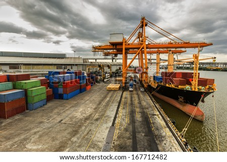 Industrial Container Cargo Freight Ship With Working Crane Bridge In Shipyard With Truck Top View