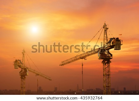 Industrial crane for construction building with sunset background.